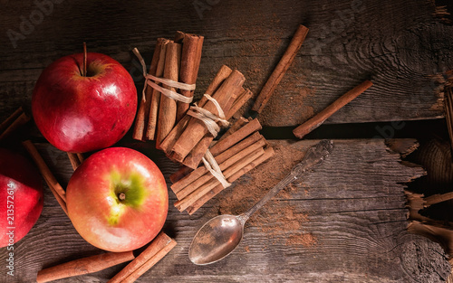 Fotografie, Obraz  Cinnamon sticks and ripe apples on a wooden background