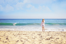 Blond Girl Watching Surfer Paddle Towards Shore