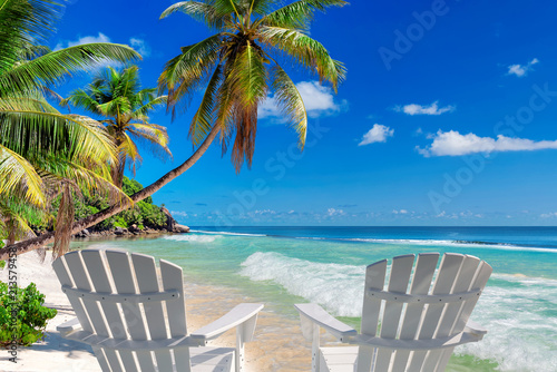 Foto auf Gartenposter Tropical strand Beach chairs on sandy beach with palm and turquoise sea. Summer vacation and travel concept.