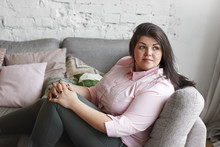 Beautiful Young Caucasian Overweight Plump Woman With Dark Hair And Nice Features Spending Lesiure Time Indoors, Relaxing On Couch At Home, Looking Sideways, Having Dreamy Facial Expression