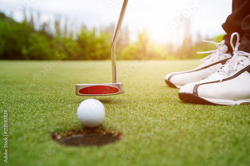 Cuadros en Lienzo  Golfer focus putting golf ball into the hole during sunset,Healthy and Lifestyle