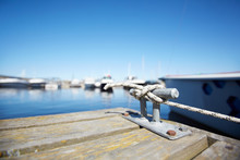 Close-up Of Metal Hook For Mooring With Knotted Rope On Wooden Pier In Yacht Club