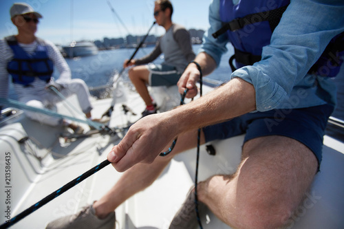 Voile Close-up of male hands pulling rope of sailboat while mooring yacht and sitting with friends on deck
