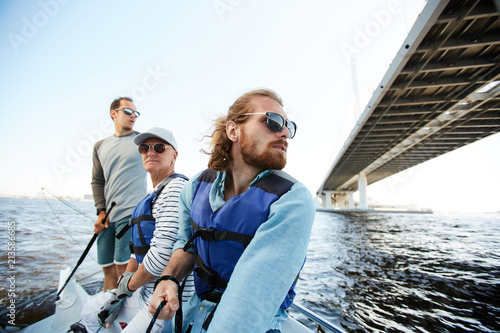 Tuinposter Zeilen Pensive dreamy men of different ages sailing yacht together and enjoying floating on river, they looking around