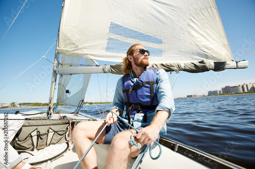Serious pensive hipster young man with beard holding rope while operating sail boat and enjoying landscape around