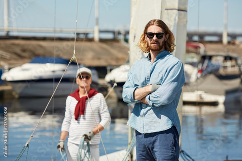 Serious hipster young bearded man in stylish sunglasses crossing arms on chest and looking at camera at yacht station, mature sailor with rope in background