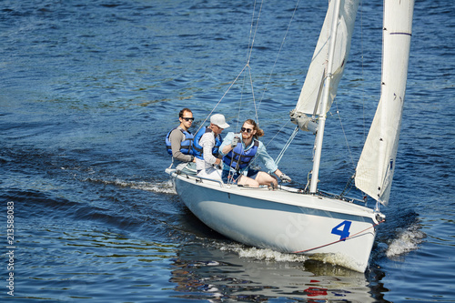 Staande foto Zeilen Group of free yachtsmen in sunglasses and life jackets sitting on sailboat deck and contemplating around while sailing at competition