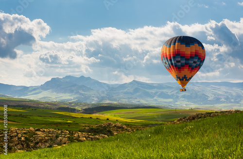 Colorful hot air balloon flying over green field
