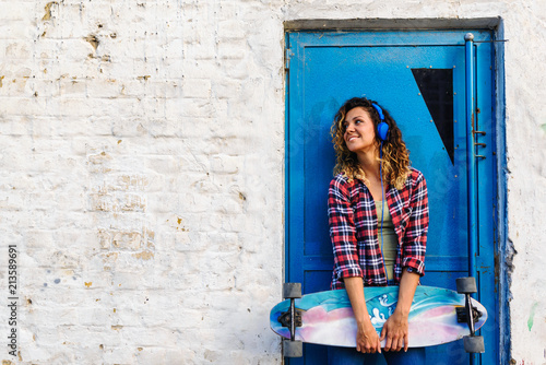 Portrait of beautiful young woman holding long-board skateboard