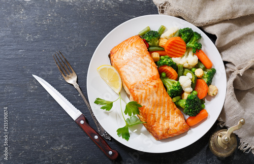 Fototapeta plate of baked salmon steak with vegetables obraz