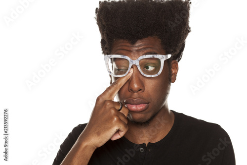 5c7f8fe0f080 Portrait of young african american man with itch in his eye on white  background