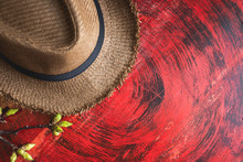 Top View Of Summer Brown Panama Straw Hat With Flower Plant On Rustic Red Wood Table.travel Concept.copy Space For Adding Text.