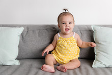 Smiling Baby Girl Sitting On Couch