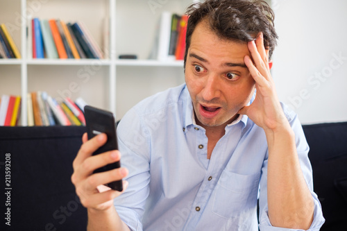 Shocked man reading fake news on the mobile phone Canvas Print
