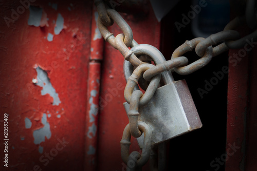 Fotografie, Obraz  Old lockpad locked on a wooden red door with rusty chain close up background