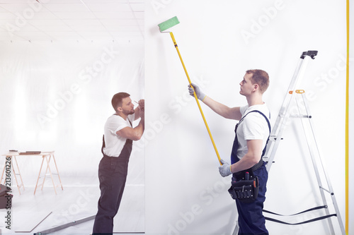 Spoed Foto op Canvas Wanddecoratie met eigen foto Decorators painting a wall with a roller in a renovating office