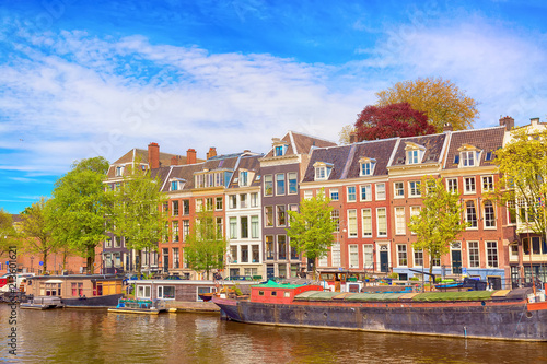 Fototapeta Amsterdam cityscape-view-of-the-canal-of-amsterdam-in-summer-with-a-blue-sky-house-boats-and-traditional-old-houses-picturesque-of-amsterdam-north-holland-the-netherlands
