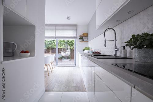 Deurstickers Wanddecoratie met eigen foto White cabinets in bright modern kitchen interior of house with terrace. Real photo