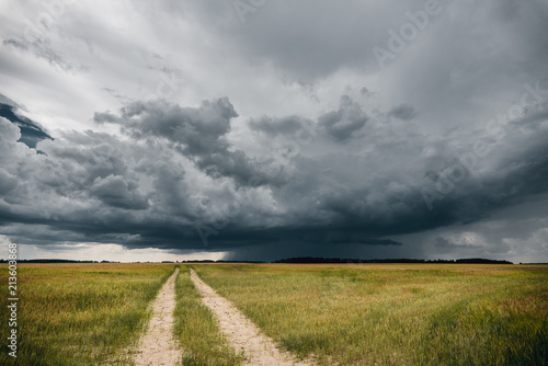 Fotografie, Obraz  A road in the fields in front of stormy clouds