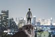 traveller on rock above megapolis