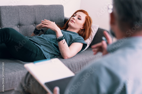 Fototapeta Sad young woman lying on a gray couch in psychologist's office