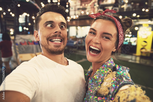 Young couple is making funny faces at evening street