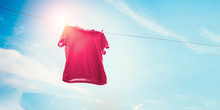 Red T-shirt On Clothes Line Against Sun And Blue Sky With Clouds.