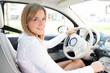 Junge Autofahrerin sympathisch lächelnd am Steuer ihres Wagens