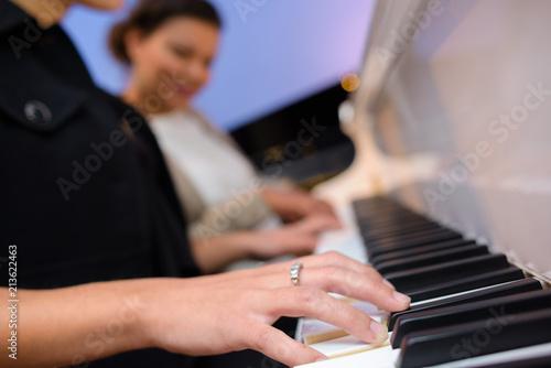 Photo  Closeup of women playing a piano duet