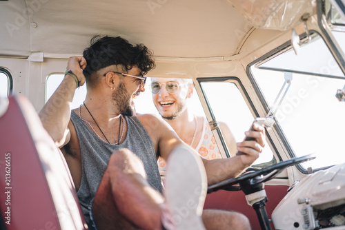 Man having fun with smartphone with friend in van