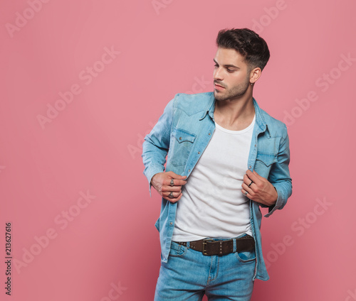 Fotografía  man holding his denim shirt's collar and looking to side