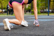 Athlete woman in running start pose outdoors in the summer.