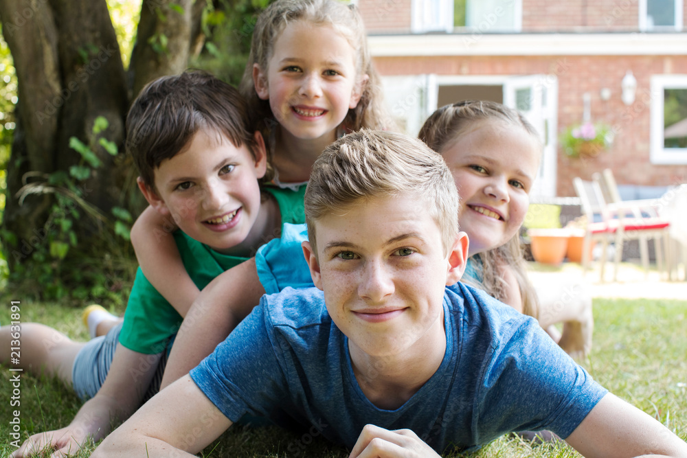 Fototapety, obrazy: Portrait Of Four Brothers And Sisters Lying In Garden At Home