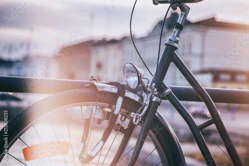 Detail of a black retro bicycle on a city background, image with vintage toning