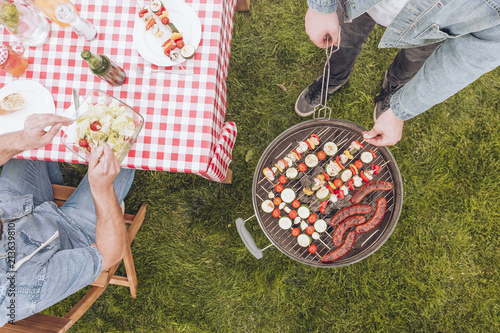 Top view on man next to grill with shashliks and sausages during outdoor party