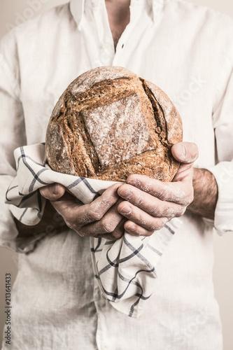 Foto Rustic crusty loaf of bread in baker man's hands