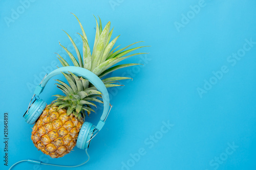 Table top view aerial image of food for summer holiday season & music background concept.Flat lay object the pineapple listening radio by blue headphone for sign of seasonal on modern paper.