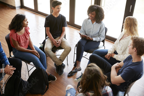 Photo Female Tutor Leading Discussion Group Amongst High School Pupils