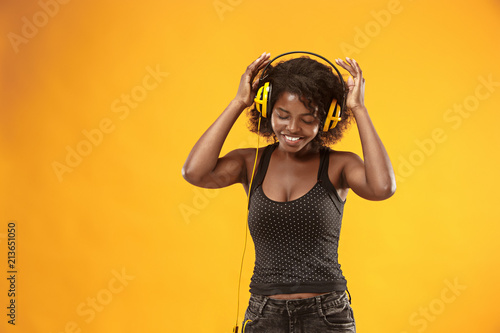Studio portrait of adorable curly girl happy smiling during photoshoot. Stunning african woman with light-brown skin relaxing in headphones - 213651050