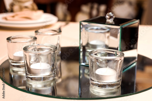 In de dag Apotheek candles in glasses and a vitreous box standing on a round mirrored tray on a table at a wedding banquet
