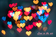 the texture is multi-colored bokeh in the form of hearts on a dark background, copy space. the concept of love, love in the air, a card about love