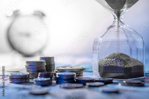 Fototapeta Sand running through the shape of hourglass on table with banknotes and coins of international currency. Time investment and retirement saving. Urgency countdown timer for business deadline concept obraz