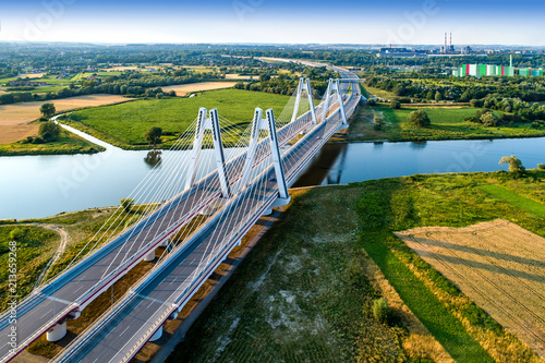 Foto auf Gartenposter Bridges New modern double cable-stayed bridge over Vistula River in Krakow, Poland. Part of the ring motorway around Krakow under construction. Aerial view at sunset. Sedzimir Steelworks in the background.