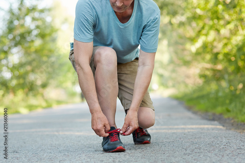 Fotobehang Jogging Cropped shot of elderly male athlete ties shoelaces, takes rest after jogging exercise, wears sportswear, poses outdoor. Man runner laces sneakers while does workout in rural area. Sport concept