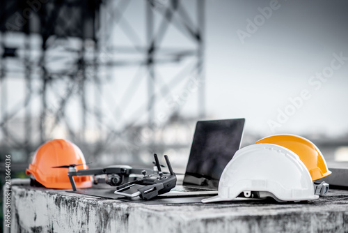 Obraz Drone, remote control, smartphone, laptop computer and protective helmet at construction site. Using unmanned aerial vehicle (UAV) for land and building site survey in civil engineering project. - fototapety do salonu
