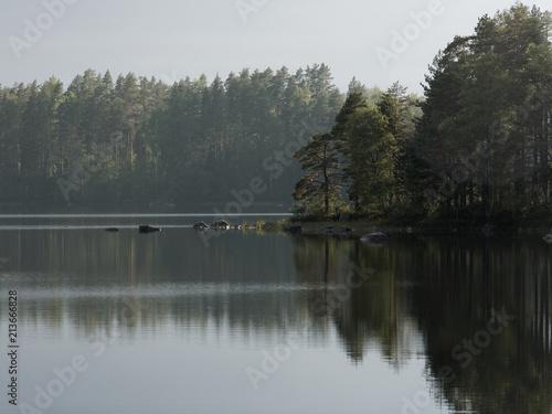 Obraz na plátne  Finnischer See an einem Regentag - die Abendsonne kommt heraus