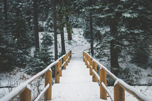 Yellow Wooden Bridge Over The Frozen Winter Lake Covered With White Snow