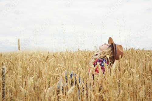 Mujer joven sentada en un campo de trigo Slika na platnu