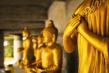 Golden Statue Of A Buddhist Monk - Close-up Of Praying Hands In Front Of Other Statues
