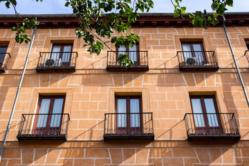 MADRID, SPAIN - MAY 15 2018: Classic Spanish architecture. Living houses in center of the city, balconies and windows covered with marquisa, colorful walls with nice material textures.